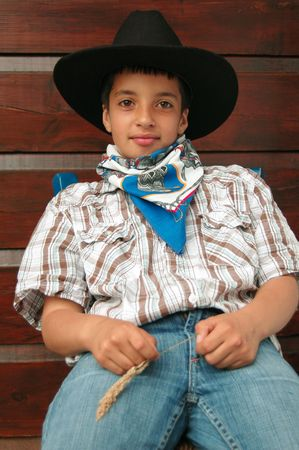 smiling little cowboy on a chair Stock Photo - 1342217