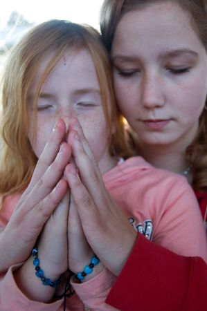 jezus: two girls are praying together (focus on hand)