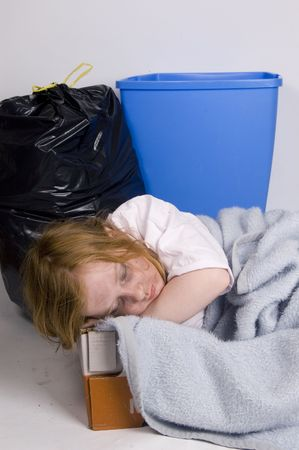 homeless kid sleeping in a box surrounded by trash Stock Photo