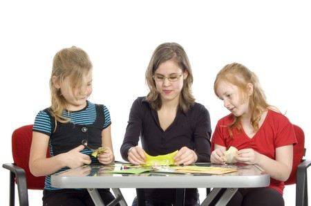 teacher is showing two little girls how to diy on white Stock Photo - 4492640