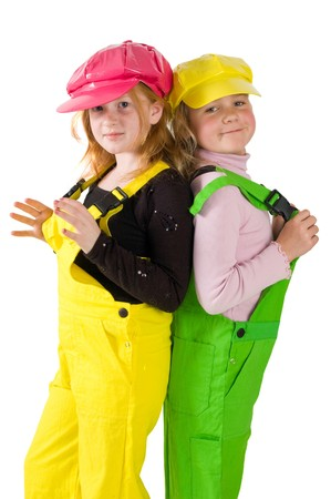 yoy: two girls wearing colorfull dungarees isolated on white Stock Photo