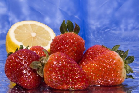 several wet strawberries and lemon with blue background Stock Photo - 4575713