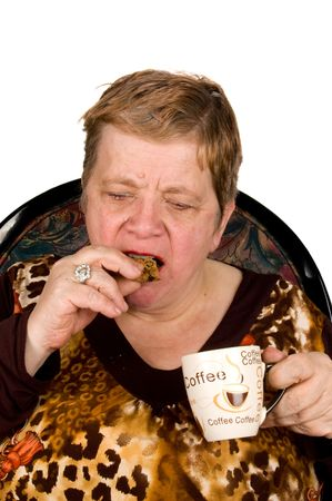 elderly woman is drinking coffee and eating a cookie isolated on white Stock Photo - 4661879