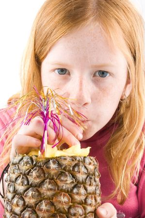 red head: red head girl is drinking from a fresh pineapple isolated on white