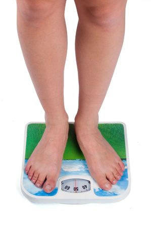 bare skinned: Leg of young caucasian female standing on bathroom scales, checking her weight