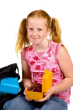 primer: schoolgirl is having grapes as lunch isolated on white