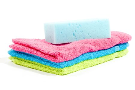 absorb: Multicolour towels stacked and body sponge isolated on white