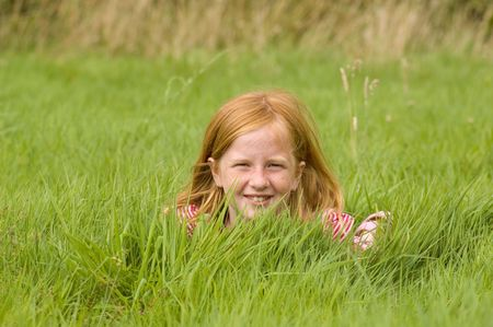 red head girl: red head girl is laying in long grass
