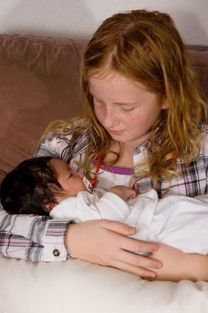 young girl  is holding her 3 weeks old baby niece photo