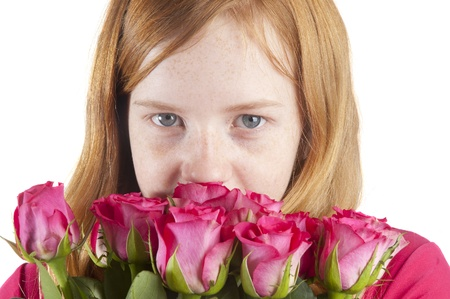 young girl is smelling at beautiful pink roses on a white background