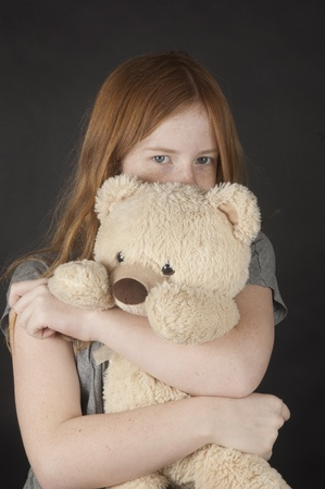 young girl is cuddling with a teddybear