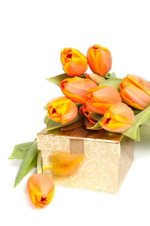 yellow orange tulips laying on a golden present Stock Photo