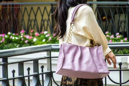 Woman wearing cream blouse carry light violet satchel on her shoulder photo