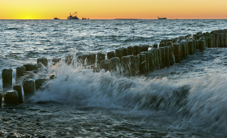 the waves beat against the breakwater, sunset on the sea, the sea at dawn, the ships on the horizon Foto de archivo