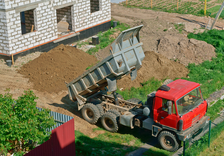 the truck and building of the house from a white brick, the dump truck brought sand on building, the dump truck near the house under construction