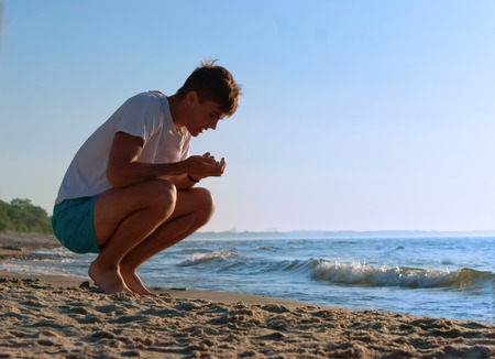 the boy collects stones on the sea, collect stones on the sea shore, the young man resting on the sea coast