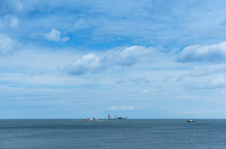 Oil drilling in the sea, ships in the sea on the horizon, calm and cloudy sky