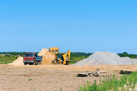 excavator and truck working on the construction site, construction equipment and a pile of sand 版權商用圖片