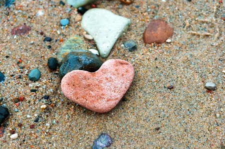 red stone heart, sea stone in the shape of a heart on the sand Stockfoto - 122883209