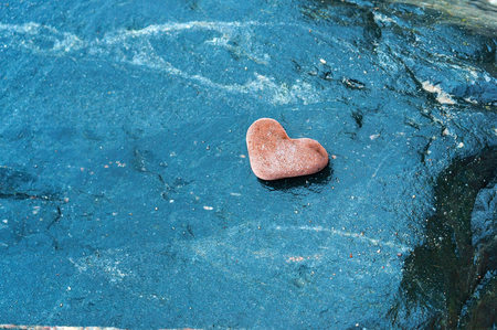 red stone heart, heart-shaped stone on dark background Stockfoto
