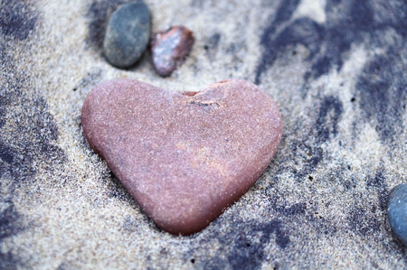 red stone heart, sea stone in the shape of a heart on the sand Stockfoto - 122927688