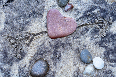 red stone heart, sea stone in the shape of a heart on the sand Stockfoto - 122883351
