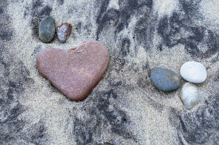 red stone heart, sea stone in the shape of a heart on the sand Stockfoto - 122927746