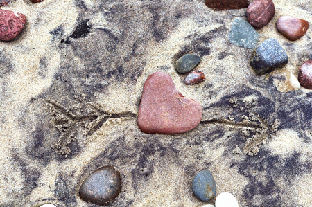red stone heart, sea stone in the shape of a heart on the sand Stockfoto - 122927763