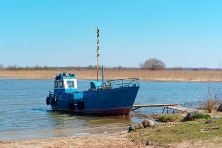 fishing boat on the shore, blue fishing boat moored