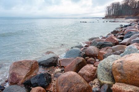 rocky seashore, stone boulders on the sea coast, cloudy inclement weather at sea Stockfoto
