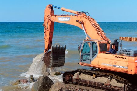 construction equipment on the seashore, construction of breakwaters in the Baltic sea, Baltic sea, Kaliningrad region, Russia, July 15, 2018