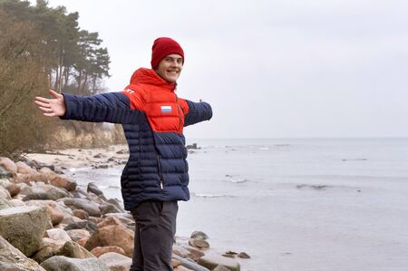young man with arms outstretched, young man with a smile on the sea, Baltic sea, Kaliningrad region, Russia, December 30, 2018