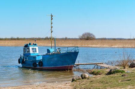 fishing boat at the shore, small fishing boat blue, Kaliningrad region, Russia, April 14, 2019