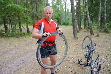 a man repairs a Bicycle in the forest, a punctured wheel at the bike, Kaliningrad region, Russia, 31 July 2019