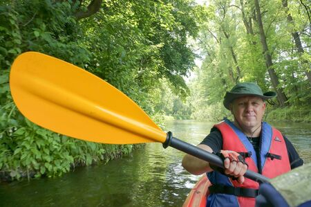 a man in a red vest on a kayak, man with yellow paddle in boat, Kaliningrad region, Russia, June 15, 2019