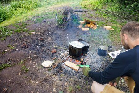 a tourist heats water in a pot on a fire, a man cooks on a fire, Kaliningrad region, Russia, June 15, 2019