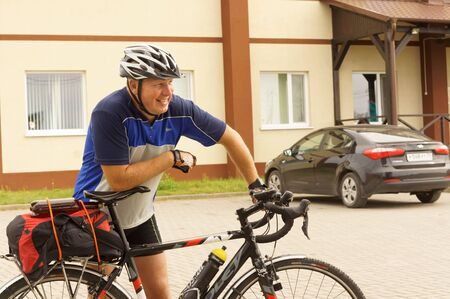 a male cyclist smiles, a man in a Bicycle helmet next to a Bicycle, Kaliningrad region, Russia, August 18, 2019