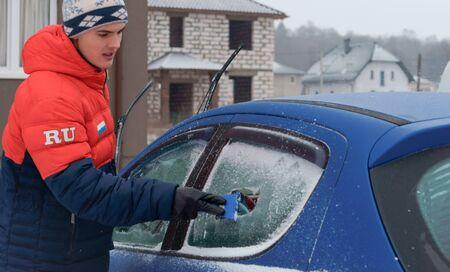 a young man cleans the car from snow, a man scrapes ice from the car window, Kaliningrad region, Russia, January 7, 2019 報道画像
