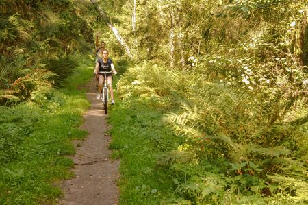 young people ride bicycles, bike ride in forest, Kaliningrad region, Russia, August 31, 2019 報道画像