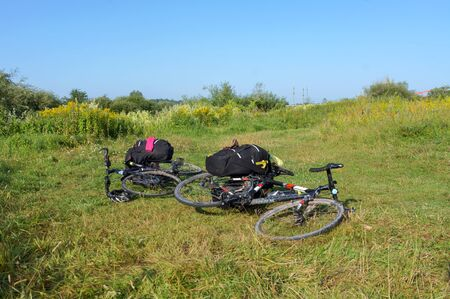 bicycles loaded with bags, travelers  bicycles lie on the grass, Kaliningrad region, Russia, August 3, 2019 報道画像