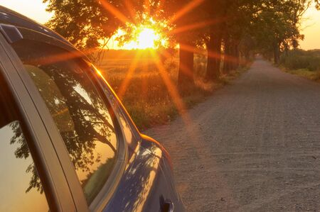 the sunset and the car, the suns rays blue cars on the road