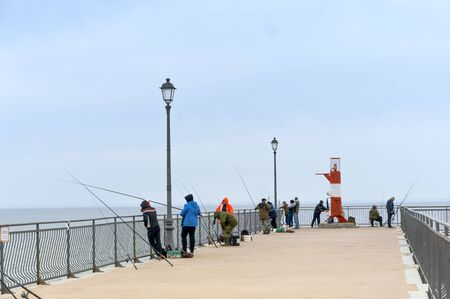 fishermen with fishing rods on the pier, fishing from the pier, Kaliningrad region, Russia, Baltic sea, may 19, 2019 報道画像