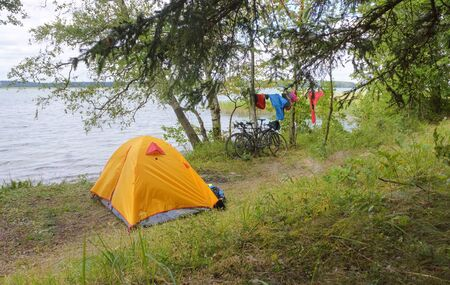 tourist tent on the shore of the pond, yellow tent on the shore of the lake, vishtynets lake, Kaliningrad region, Russia, July 31, 2019 報道画像