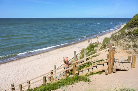 man climbs stairs, sea beach and stairs descent to the sea, Kaliningrad region, Russia, Baltic sea, July 14, 2019