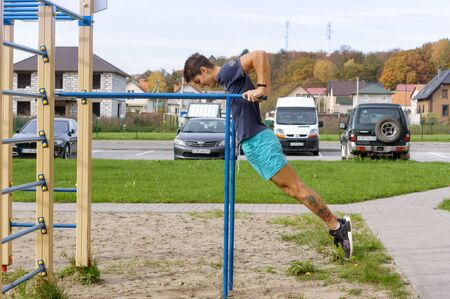sports man on uneven bars, a man trains on the Playground, Kaliningrad region, Russia, October 19, 2019