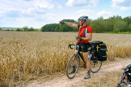 cyclist tourist looking for the road, bike traveler got lost on the way, Kaliningrad region, Russia, July 30, 2019