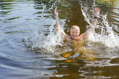 a man splashes water, cheerful resting in the pond, Kaliningrad region, Russia, 29 July 2019