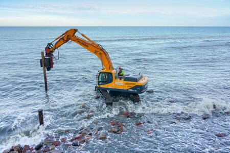 manipulator works with piles, construction of breakwaters in the sea, Baltic sea, Svetlogorsk, Kaliningrad region, Russia, November 17, 2019