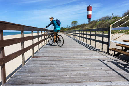 a young man on the boardwalk, Cycling along the embankment, Baltic sea, Kaliningrad region, Russia, may 10, 2020