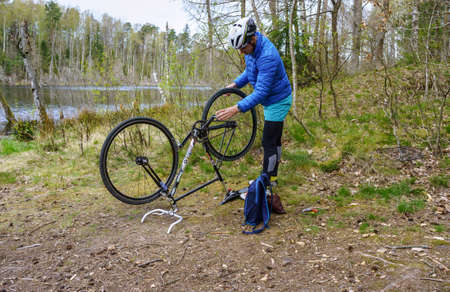 a man repairing a Bicycle in a field, a puncture of a Bicycle camera on the way, Kaliningrad region, Russia, April 26, 2020 新闻类图片